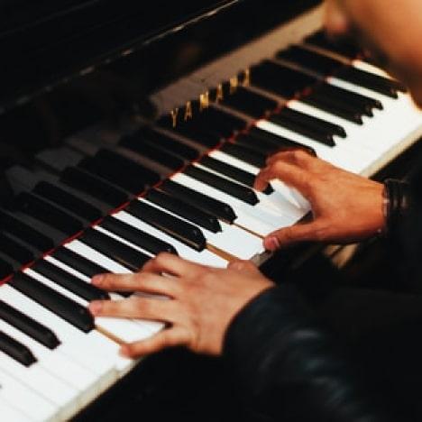 close up of man performing on yamaha piano
