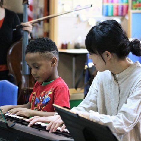 teacher teaching student how to play piano