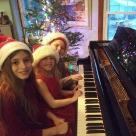 three little girls playing the piano wearing christmas hats